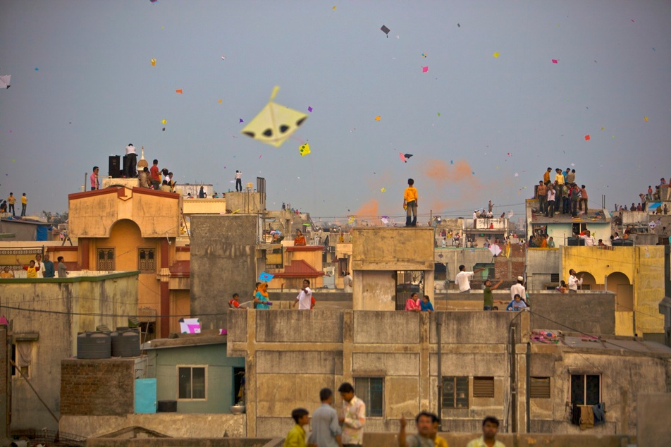 Indian people fly kites on thier roof tops during the festival of 'Makara Sankranti' in Vadodra, Gujarat. India.The day on which the sun begins its journey northwards is referred to as Makara Sankranti. It marks the beginning of the gradual increase of the duration of the day. Traditionally, this has been one of many harvest days. In India, this festival is celebrated for innumerable reasons depending on the climate, agricultural environment, cultural background and location.